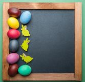 Blackboard and colorful Easter eggs on it. View from above stock photography