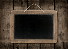 Blackboard on a dark wood wall background Stock Photos