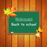 Blackboard decorated with autumn maple leaves on background a wo Royalty Free Stock Images