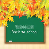 Blackboard decorated with autumn maple leaves Stock Photos