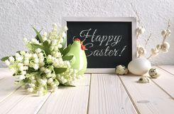 Blackboard decorated with ceramic hen, eggs and and lily of the. Easter composition with blackboard decorated with ceramic hen, eggs and and lily of the valley Stock Photo