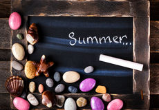 Blackboard decorated with sea objects shaped candies and pebbles Stock Image