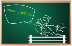 A blackboard with a drawing of a boy performing show jumping Stock Photo