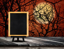 Blackboard with easel on grunge plank wooden table top at spooky Stock Photo