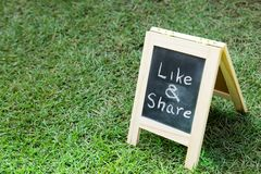 Blackboard with easel and wording like and share on green grass Royalty Free Stock Photo