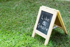 Blackboard with easel and wording like and share on green grass. Background Stock Photos