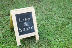 Blackboard with easel and wording like and share on green grass. Background Royalty Free Stock Photo