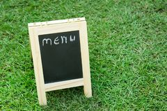 Blackboard with easel and wording menu on green grass. Background Royalty Free Stock Photos