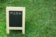 Blackboard with easel and wording menu on green grass background. Blackboard with easel and wording menu on green grass Royalty Free Stock Image
