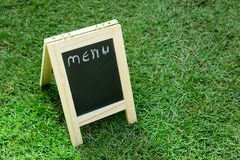 Blackboard with easel and wording menu on green grass. Background Stock Photography