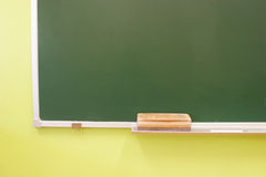 Blackboard with eraser. Part of a blackboard with eraser isolated on a green background Stock Photos
