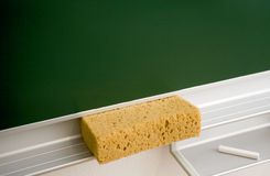 Blackboard eraser and chalk. A blackboard, sponge eraser and white piece of chalk Royalty Free Stock Image