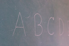 Blackboard with the first letters of the alphabet written on it Stock Photography