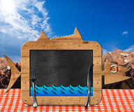 Blackboard Fish Shaped with Fishing Nets. Blackboard in the shape of fish with blue waves and silver cutlery on a table with checkered tablecloth and fishing Stock Photography