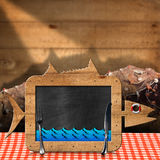 Blackboard Fish Shaped with Fishing Nets. Blackboard in the shape of fish with blue waves and silver cutlery on a table with checkered tablecloth and fishing Stock Photos