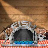 Blackboard Fish Shaped with Fishing Nets. Blackboard in the shape of fish and serving dome with silver cutlery on a table with checkered tablecloth and fishing Stock Photography