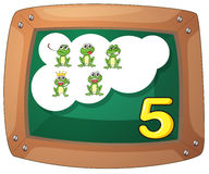 A blackboard with five frogs Stock Images