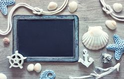 Blackboard  with frame made of sea shells, stones, rope and star Royalty Free Stock Images
