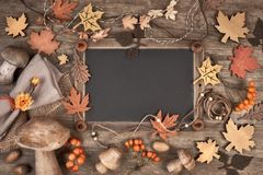 Blackboard framed with Autumn decorations on wood, space. Blackboard framed with Autumn decorations on wood. Top view, toned image, space for your text Stock Photography