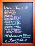 Spanish tapas bar in Seville, Spain. Blackboard with the gastronomic specialties of the bar placed on the facade, Seville, Andalusia, Spain Royalty Free Stock Images