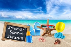 Blackboard sommer sonne strand on beach. Blackboard with german words Sommer Sonne Strand english translation: summer sun beach and beach supplies accessory on Stock Images