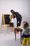 At the blackboard girl with a tutor draw shapes, another girl sitting at the table Royalty Free Stock Photo