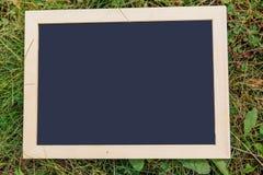 Blackboard on green grass Stock Photos