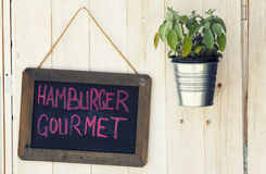 Blackboard Hamburger Gourmet and pot with plant on wooden surface royalty free stock photography
