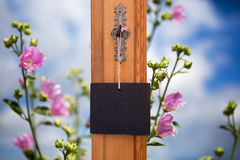 Blackboard hanging on key in front of field of flowers stock photography