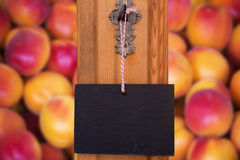 Blackboard hanging on key in front of peaches Stock Photo