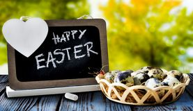 Blackboard and eggs on wooden table. Easter background. royalty free stock photography