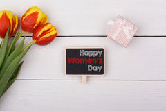 Blackboard with Happy Women's Day,. Bouquet of tulips and a gift with a bow on the table Royalty Free Stock Photos