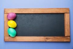 Blackboard i kolorowi Wielkanocni jajka wokoło go na widok fotografia royalty free