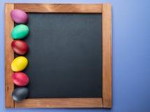 Blackboard i kolorowi Wielkanocni jajka wokoło go na widok zdjęcie stock