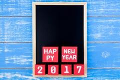 Blackboard i Szczęśliwy nowy rok 2017 liczb na czerwonych papierowego pudełka sześcianach Zdjęcia Stock