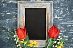 Blackboard i wiązka czerwoni tulipany i leluja dolina kwitniemy obrazy royalty free