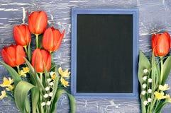 Blackboard i wiązka czerwoni tulipany i leluja dolina kwitniemy Zdjęcia Royalty Free