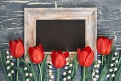 Blackboard i wiązka czerwoni tulipany i leluja dolina kwitniemy Zdjęcie Stock