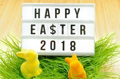 Blackboard with the inscription Happy Easter 2018 in German Happy Easter 2018, dollar sign, bouquet of flowers and Easter bunnies. In the grass on a bamboo Stock Image