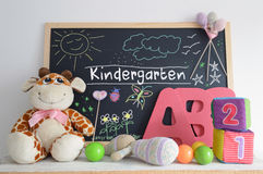 Blackboard in a kindergarten classroom and some baby stuff. A blackboard in a kindergarten classroom. Some baby stuff. Foam letters, cubes, and hand made Stock Photography