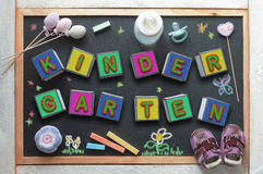Blackboard in a kindergarten classroom and some baby stuff. Some letter cubes forming the word kindergarten, a baby bottle, a pacifier, some toys and sneakers stock photo