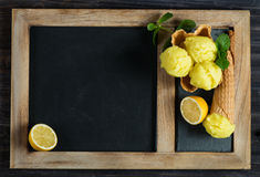 Blackboard and lemon ice cream, above view. Lemon sorbet in a wafer basket and in a cone on a black chalkboard for menu with copy space for your text stock image