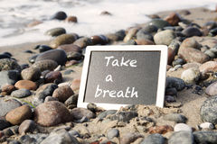 Blackboard lying on beach with the words Take A Breath. Blackboard lying between stones on sandy beach with the words Take A Breath stock image