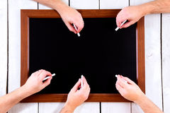 Blackboard with many hands with chalk Royalty Free Stock Photo