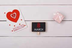 Blackboard with 8 march tag, a gift and a card with red hearts. On a white table Stock Photos
