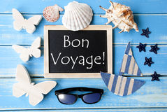 Blackboard With Maritime Decoration, Bon Voyage Means Good Trip. Flat Lay Of Chalkboard On Blue Wooden Background. Nautical Summer Decoration As Holiday Greeting Royalty Free Stock Photos