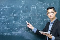 Instructors are teaching mathematics. Right hand holds chalk. Blackboard with mathematical content, Writing with a variety of colors. To stimulate teaching Stock Photography