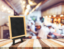 Blackboard menu with easel on wooden table with blur open kitche Royalty Free Stock Photo