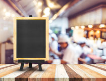 Blackboard menu with easel on wooden table with blur open kitche Stock Photography