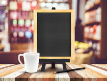 Blackboard menu with easel on wooden table with coffee cup and p Stock Photography